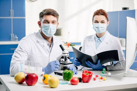 molecular nutritionists in medical masks looking at camera in lab