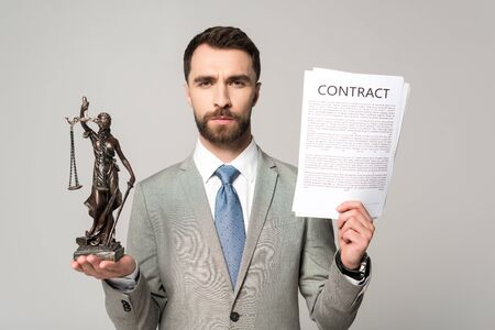 confident lawyer holding contract and themis statue while looking at camera isolated on grey