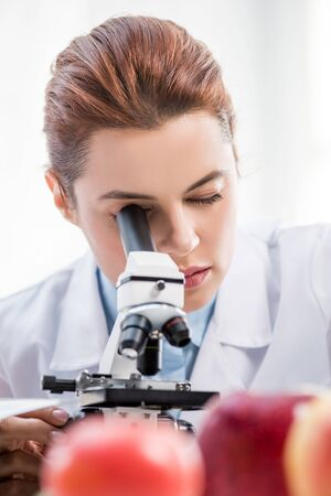 selective focus of molecular nutritionist using microscope in lab Stok Fotoğraf