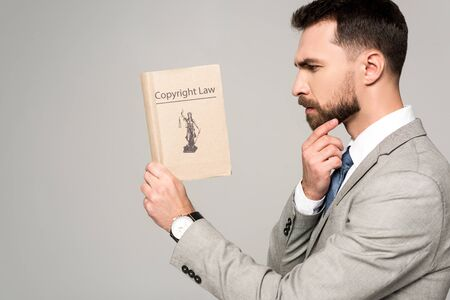 side view of serious lawyer reading book with copyright law title isolated on grey