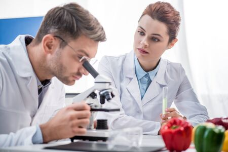 selective focus of molecular nutritionist holding test tube and looking at his colleague with microscope