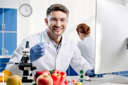 selective focus of smiling molecular nutritionist holding test tube Stok Fotoğraf