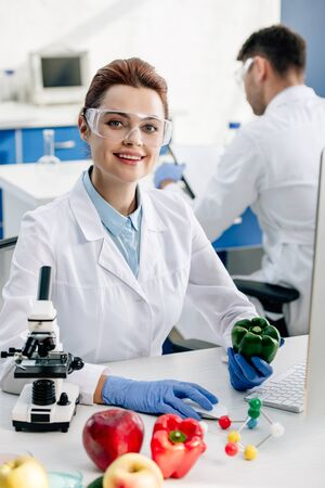 smiling molecular nutritionist holding bell pepper and looking at camera