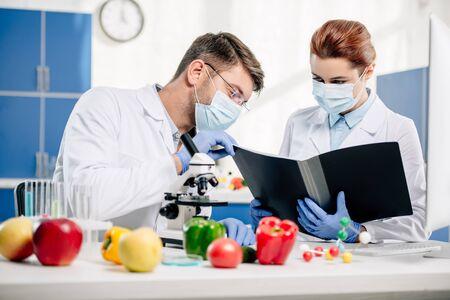 selective focus of molecular nutritionists in medical masks looking at folder Stok Fotoğraf