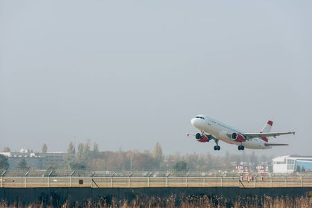 Jet plane above airport runway with cloudy sky at background 写真素材