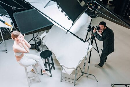 Overhead view of beautiful model and videographer working in photo studio with spotlights Stock Photo