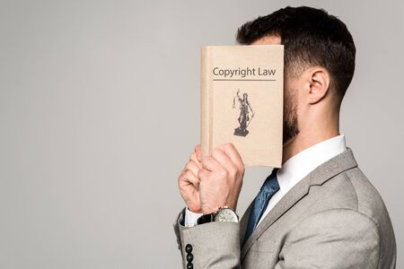 side view of lawyer obscuring face with copyright law book isolated on grey
