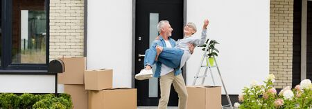 panoramic shot of mature man holding smiling woman near new house Stock Photo