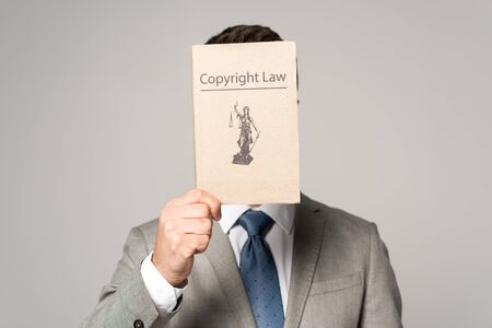front view of lawyer obscuring face with copyright law book isolated on grey