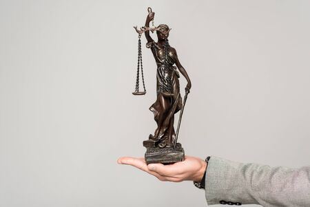 partial view of lawyer holding themis statue isolated on grey