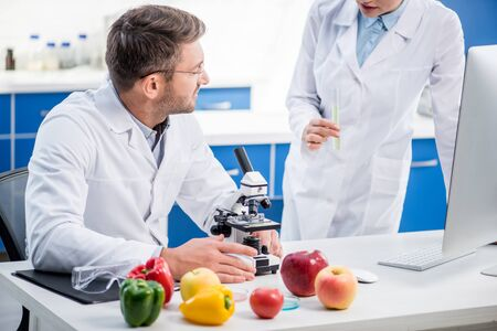cropped view of molecular nutritionist talking with colleague in lab