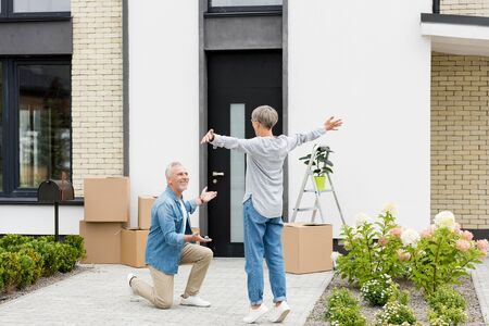 mature man pointing in with hand and holding keys of new house to woman with outstretched hands