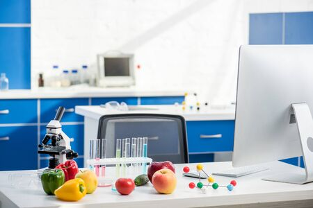 microscope, fruit, vegetables, test tubes and computer on table in lab