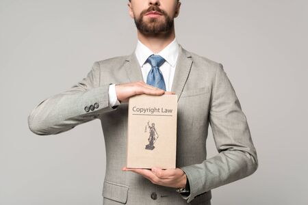 partial view of lawyer holding book with copyright law title isolated on grey