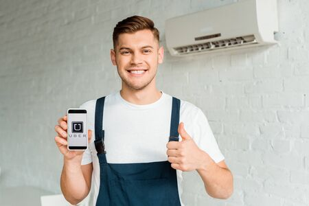 KYIV, UKRAINE - DECEMBER 4, 2019: cheerful installer showing thumb up while holding smartphone with uber app on screen