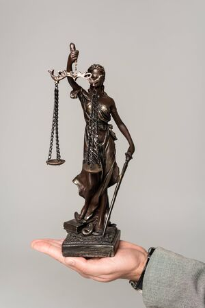 cropped view of lawyer holding themis statue isolated on grey