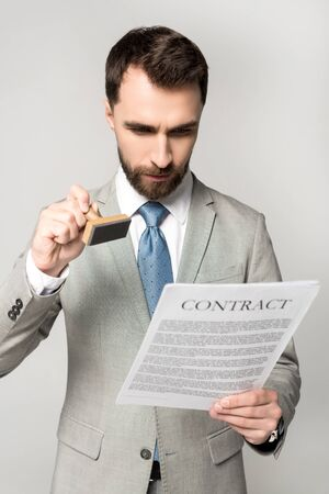 serious lawyer putting stamp on contract isolated on grey