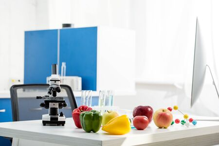 microscope, fruit, vegetables, test tubes on table in lab