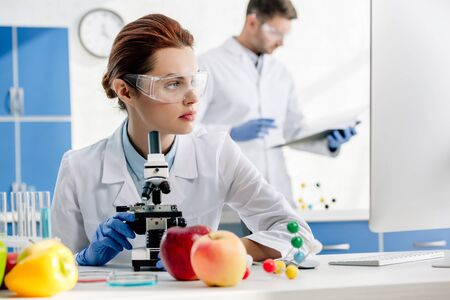 selective focus of molecular nutritionists looking at computer and colleague on background