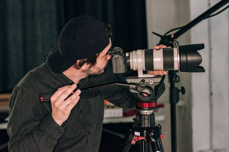 Side view of videographer working with camera in photo studio 스톡 콘텐츠