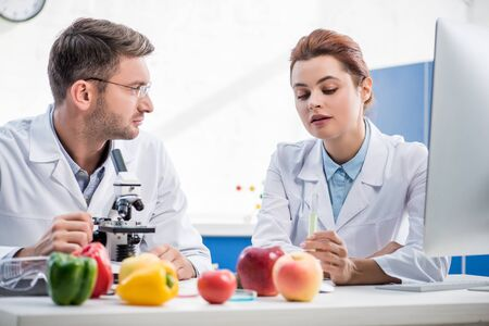 molecular nutritionists in white coats talking in lab