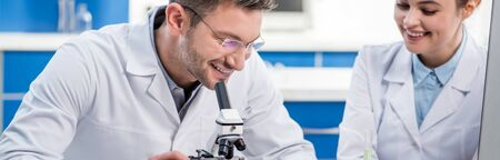panoramic shot of smiling molecular nutritionists using microscope in lab