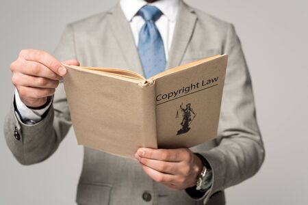 cropped view of lawyer holding book with copyright law title isolated on grey Zdjęcie Seryjne