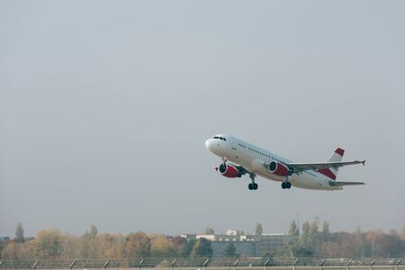 Commercial plane departure on airport airfield with cloudy sky at background 写真素材