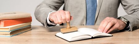 cropped view of lawyer putting stamp in notebook isolated on grey, panoramic shot