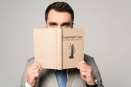 serious lawyer looking at camera while holding book with copyright law title isolated on grey