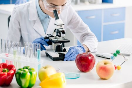 cropped view of molecular nutritionist using microscope and sitting at table