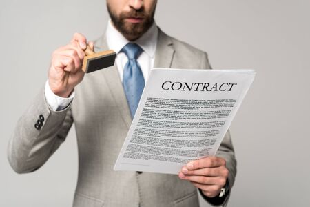 cropped view of lawyer putting stamp on contract isolated on grey