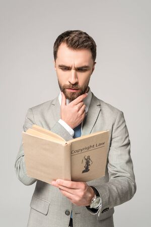 serious lawyer reading book with copyright law title isolated on grey