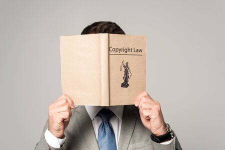 lawyer obscuring face with copyright law book isolated on grey Zdjęcie Seryjne