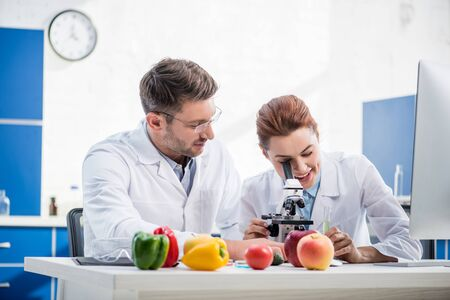 smiling molecular nutritionist using microscope and her colleague looking at her
