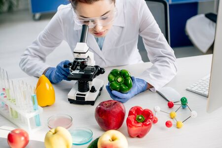 cropped view of molecular nutritionist using microscope in lab