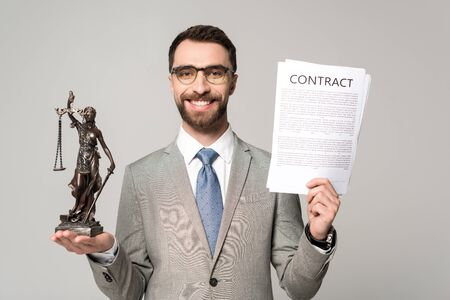 handsome lawyer holding contract and themis statue while smiling at camera isolated on grey Zdjęcie Seryjne