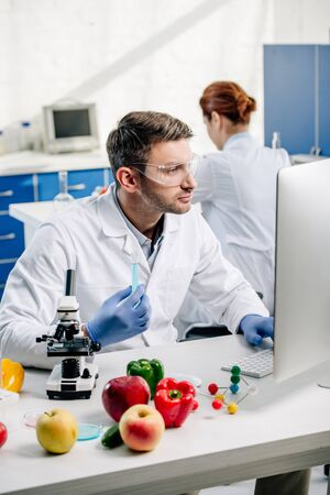 molecular nutritionist holding test tube and using computer in lab
