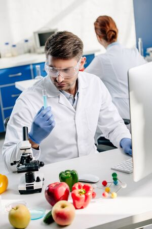 molecular nutritionist in goggles looking at test tube in lab