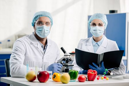 molecular nutritionists in medical masks looking at camera in laboratory