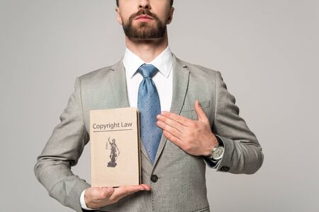 partial view of lawyer holding hand near heart and book with copyright law title isolated on grey