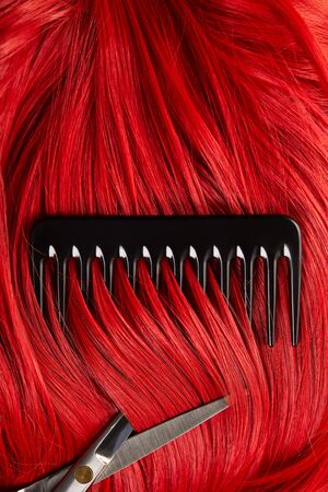 Top view of red hair with scissors and comb