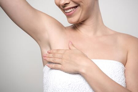 cropped view of smiling woman touching underarm isolated on grey