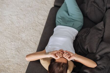 top view of tired woman touching eyes while lying on sofa