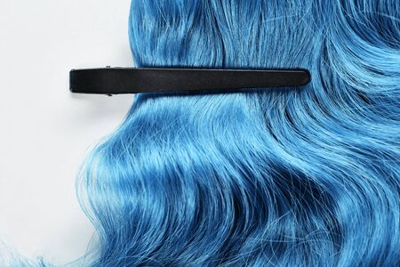 Top view of clamp on blue hair on white background