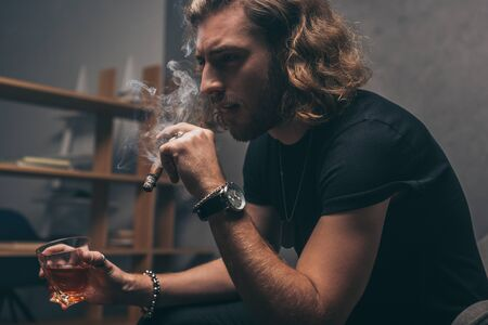 fashionable businessman in black outfit smoking cigar and drinking whiskey