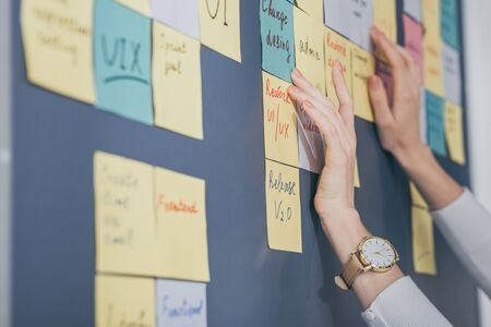 cropped view of businesswoman touching sticky notes with letters in office Stock Photo