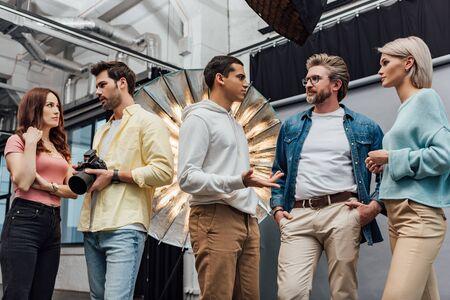 art director standing with hands in pockets near coworkers in photo studio Imagens