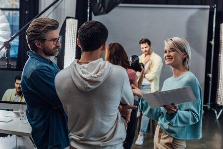 selective focus of happy woman looking at coworker near art director in photo studio Banco de Imagens - 138254857