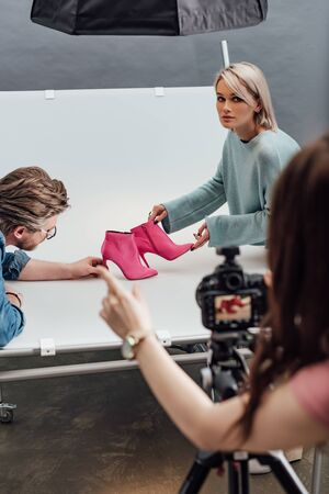 cropped view of photographer pointing with finger near attractive assistant and art director holding pink shoes Banco de Imagens - 138254871